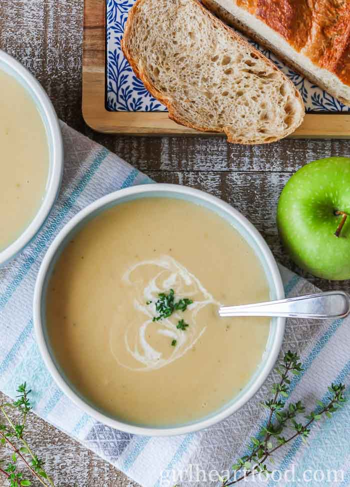 An overhead shot of a bowl of creamy parsnip and apple soup garnished with chives, alongside apple and bread.