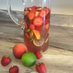 Large jug of strawberry peach sangria alongside some fruit.