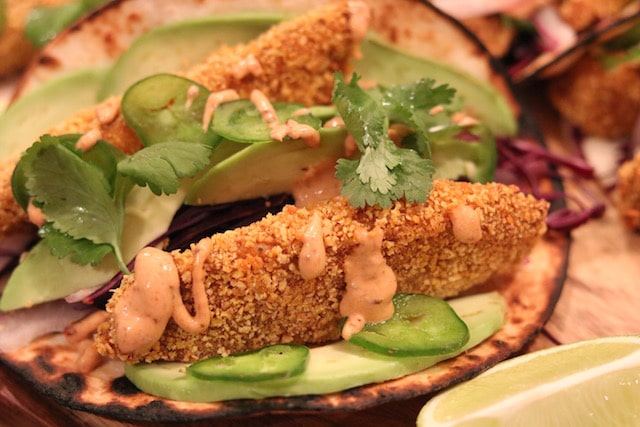 Panko crusted tilapia fish taco with garnish and chipotle sauce.