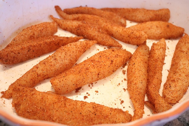 Strips of raw talapia coated in spice mixture in a white dish.