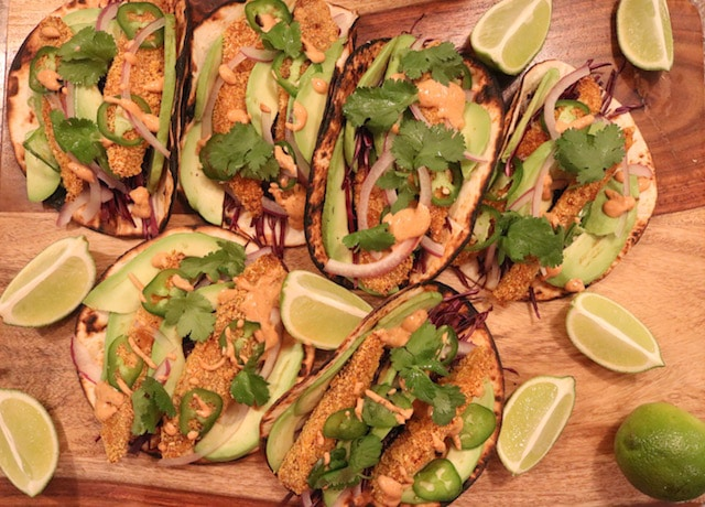 Oven baked fish tacos on a wooden board surrounded by lime wedges.