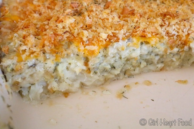 Close up of cod au gratin in a dish with some cut out to show interior.