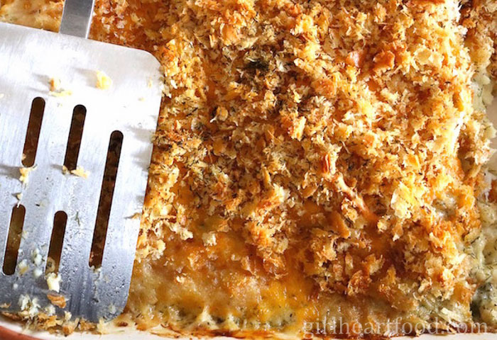 Close-up of the top of baked cod au gratin with a spatula resting on it.