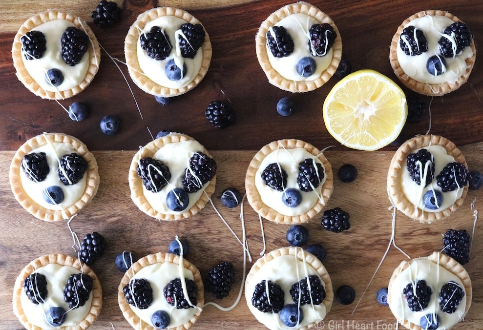 An overhead shot of A close up of Lemon Cream Tarts topped with fresh berries alongside a cut lemon.
