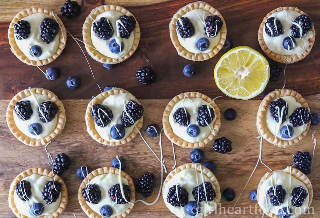 Plenty of lemon cream tarts garnished with fresh berries on a wooden board next to a cut lemon.