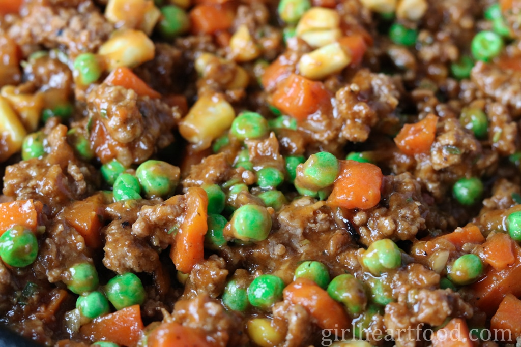 Close-up of a cooked lamb and veggie mixture that goes in a classic shepherd's pie recipe.