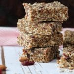Stack of crunchy granola bars stacked on top of each other next to almonds and cranberries.