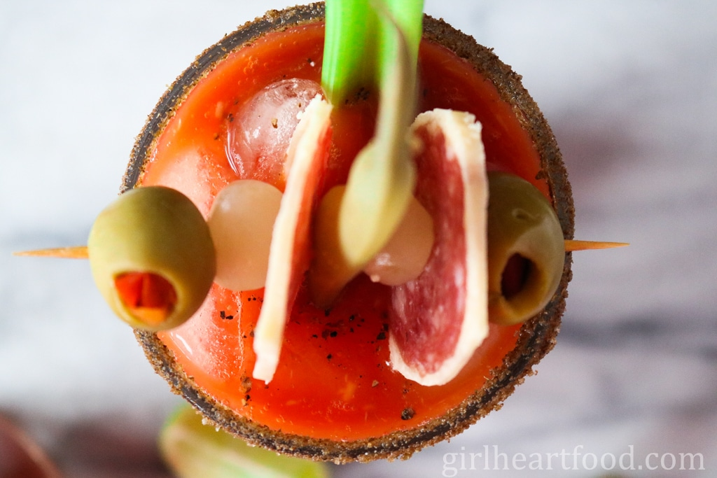 An overhead shot of a caesar cocktail garnsihed with olives, salami, pickled onions, green bean and celery.