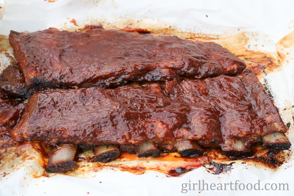 Oven baked ribs that are brushed with bbq sauce.