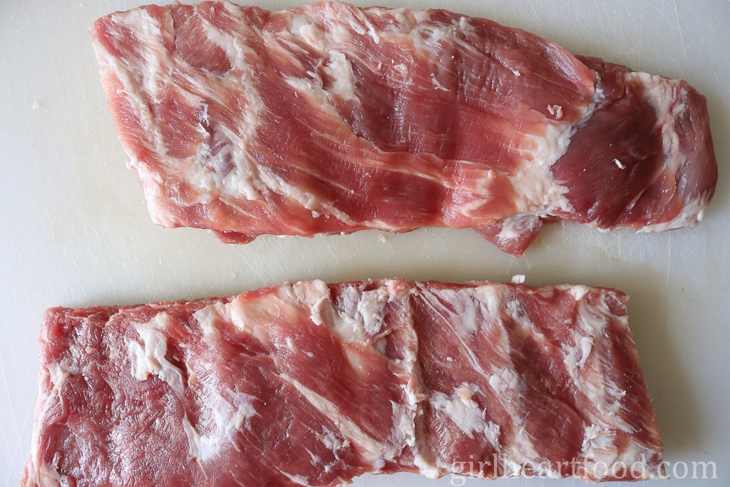 Uncooked pork ribs on a cutting board.