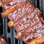 Rack of pork ribs brushed with bbq sauce on the grill.