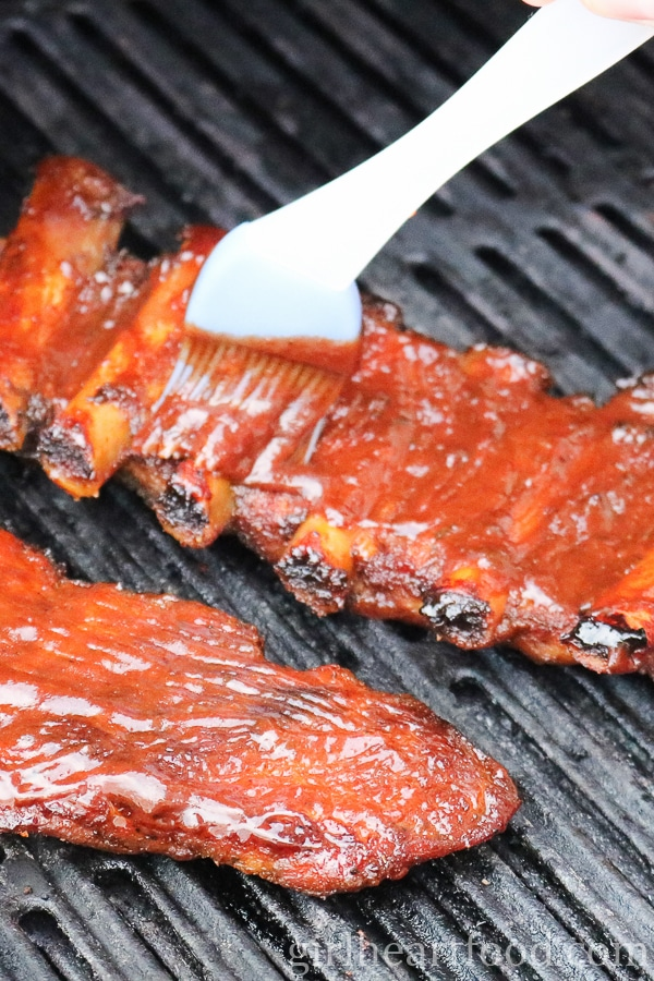 Ribs on the grill that are being brushed with bbq sauce.
