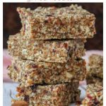 Tall stack of homemade granola bars next to an almond and cranberry with text.
