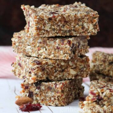 Stack of four no bake granola bars next to an almond and dried cranberry.