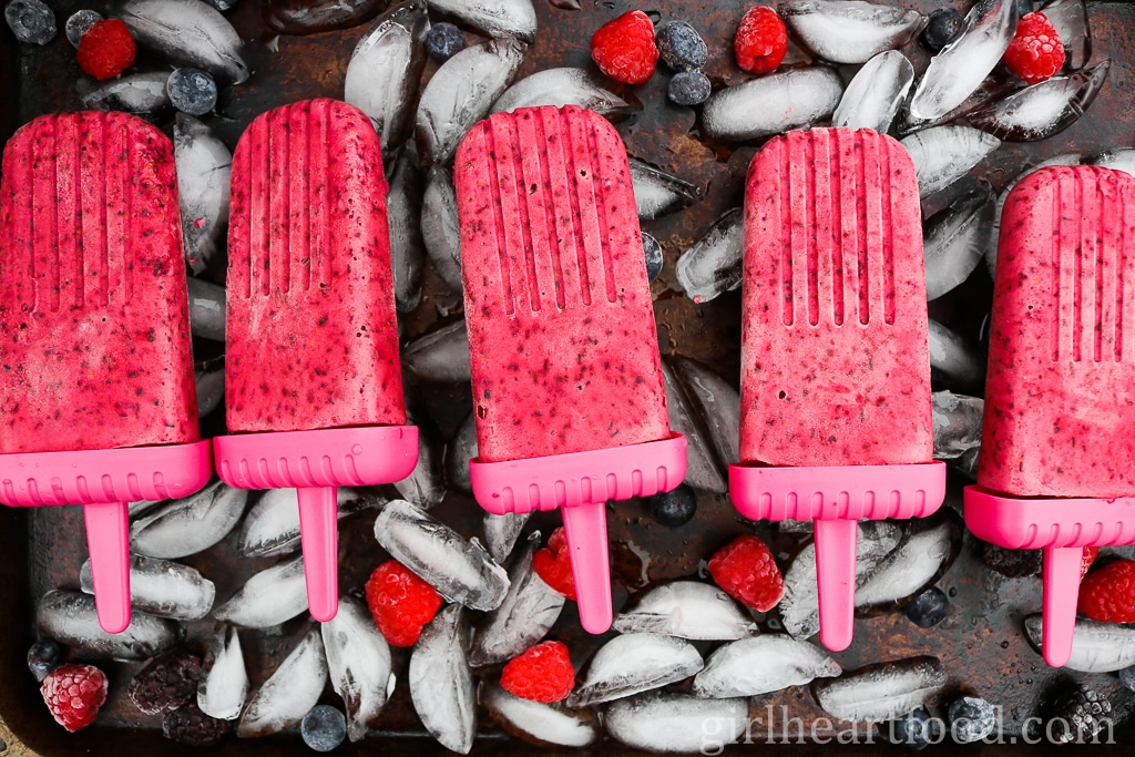 Five berry ice pops on a tray on top of ice and alongside some berries.