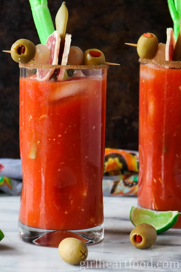 A close up of the best caesar cocktail recipe garnished with celery, green bean, pickled onion, olives and salami.