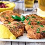 A plate of traditional pork schnitzel garnished with fresh parsley and next to lemon wedges.