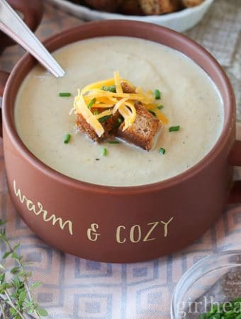 A bowl of creamy cauliflower soup garnished with croutons, cheese and chives.