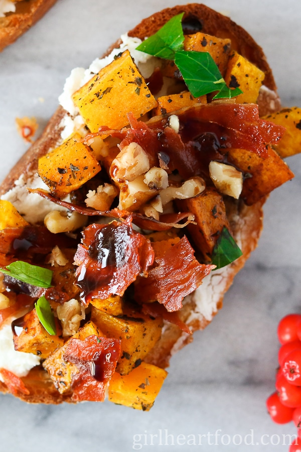 A close up of Roasted Acorn Squash Crostini with Crispy Prosciutto and Goat Cheese.