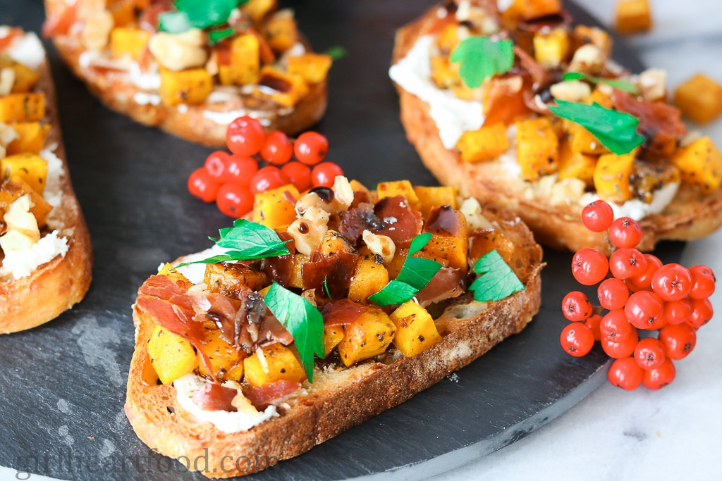 A tray of Roasted Acorn Squash Crostini with Crispy Prosciutto and Goat Cheese.
