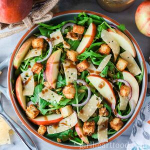 Round dish of apple and gouda mixed green salad with croutons and vinaigrette drizzled over top.