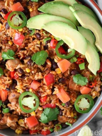 This one pot healthy southwest chicken and rice skillet is packed with bell peppers, corn and black beans and garnished with jalapeno, avocado, and cilantro.