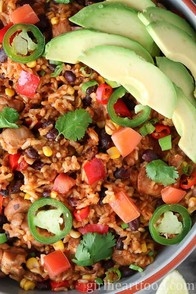 A close up overhead shot of southwest chicken and rice skillet garnished with jalapeno, tomato, cilantro and avocado