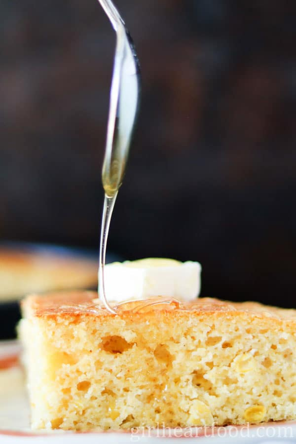 A slice of cheesy skillet cornbread with a dabble of butter and drizzled with honey.