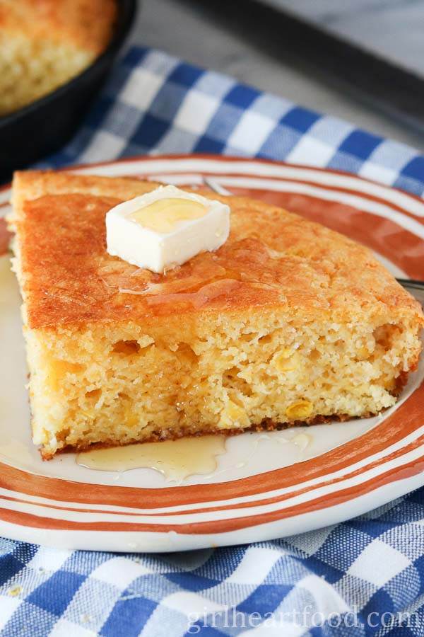 A slice of cornbread on a plate with a dabble of butter and drizzled with honey.