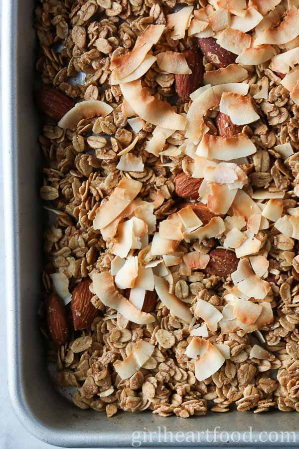 An overhead shot of a pan of easy homemade granola with almonds and coconut.