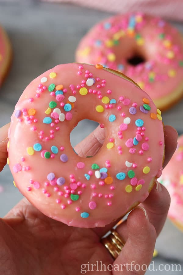 Someone holding up a pink glazed donut with colourful sprinkles.