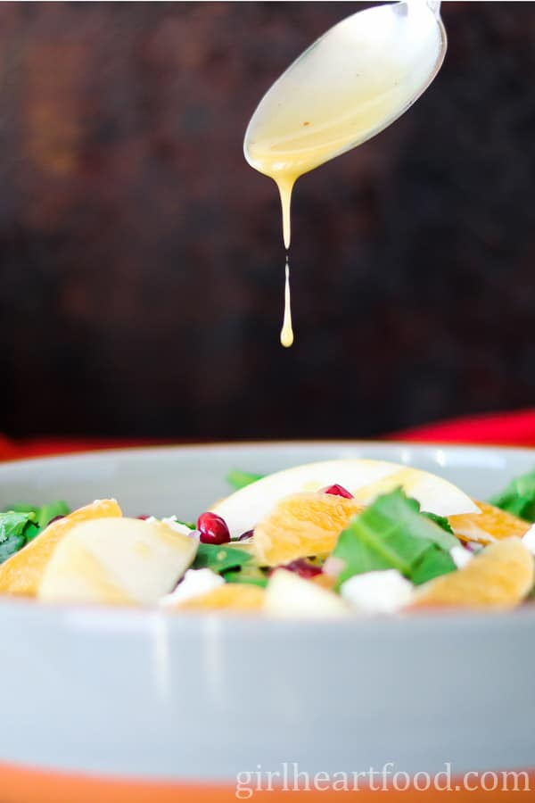 A spoon drizzling honey Dijon vinaigrette over a green salad.