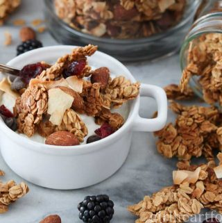 Homemade granola in a white dish alongside some more granola spilling out of a jar.