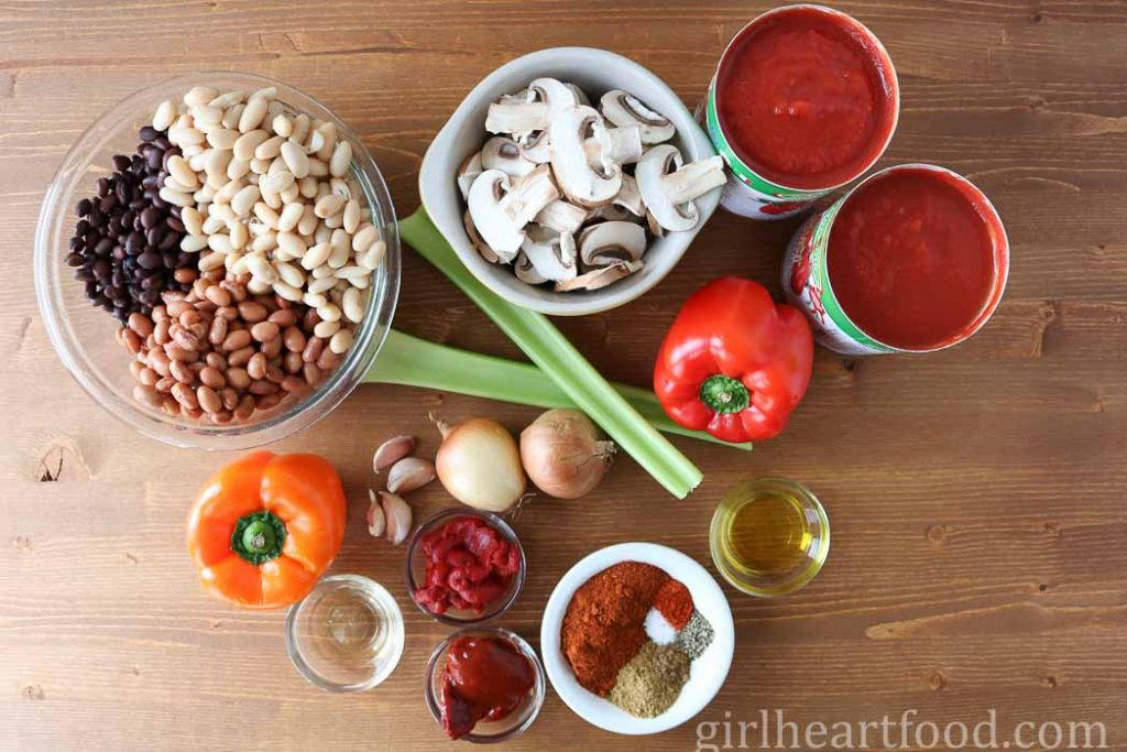 Ingredients for a meatless chili recipe on a wooden board.