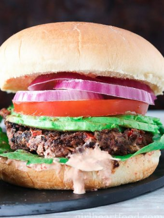Vegan black bean burger garnished with onion, tomato, avocado, lettuce and sauce.