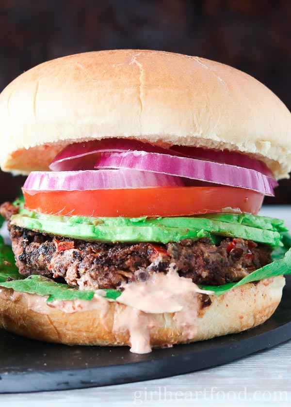 A close up shot of a black bean burger garnished with onion, tomato, avocado, lettuce and sauce.