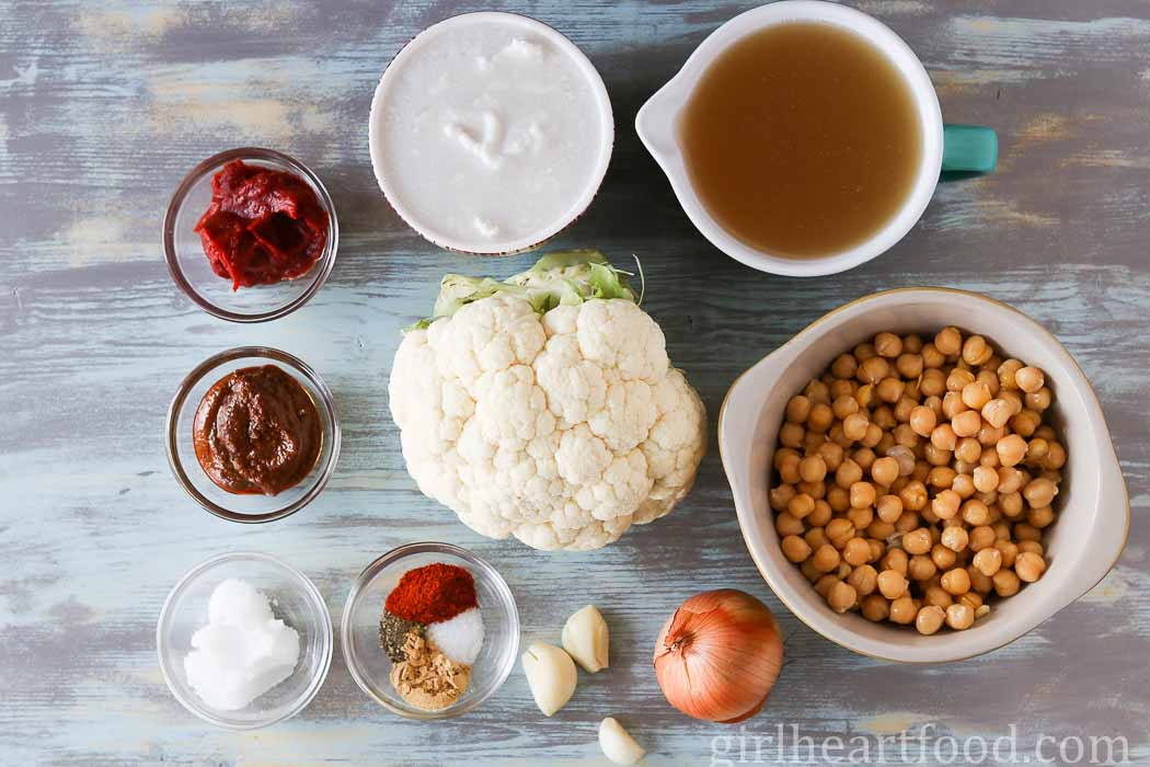 Ingredients for chickpea cauliflower curry on a wooden board.
