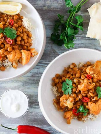 An overheat shot of two bowls of chickpea cauliflower curry garnisheed with chili, cilantro and lemon.
