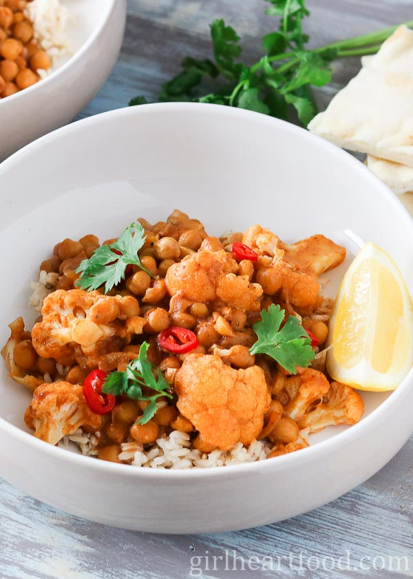 Bowl of chickpea cauliflower curry garnished with chili pepper, cilantro and lemon.