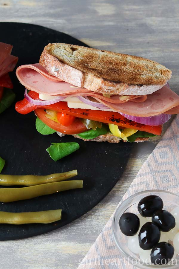 A mortadella sandwich next to pickled green beans, black olives and pickled onions.
