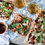 Overhead shot of bbq chicken flatbread pizza with some wine, bowl of bbq sauce and small bowl of hot peppers.