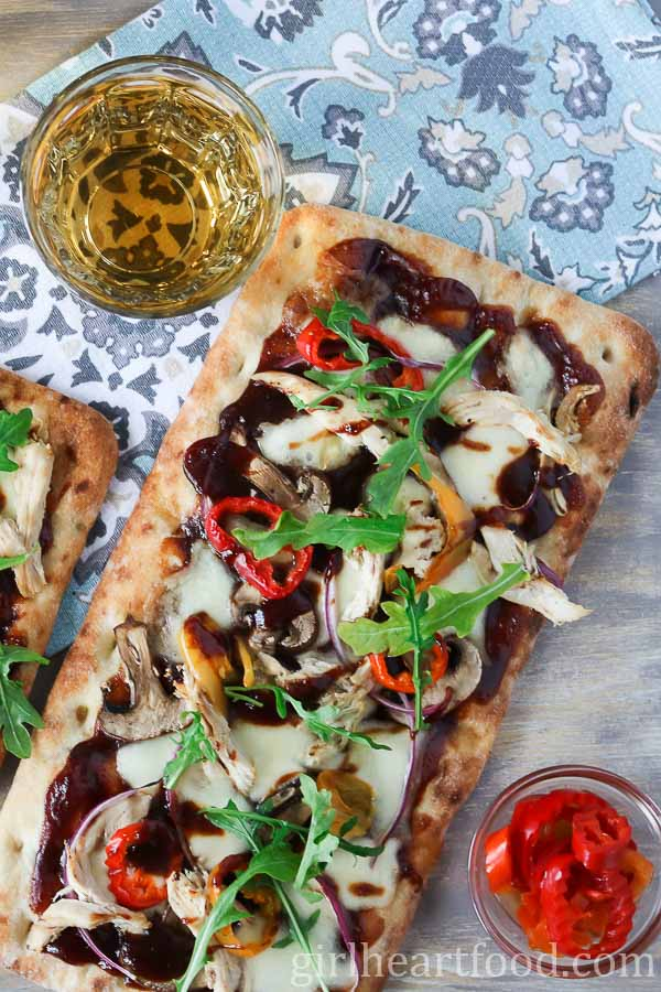 An overhead shot of bbq chicken flatbread pizza alongside wine and a dish of hot peppers.