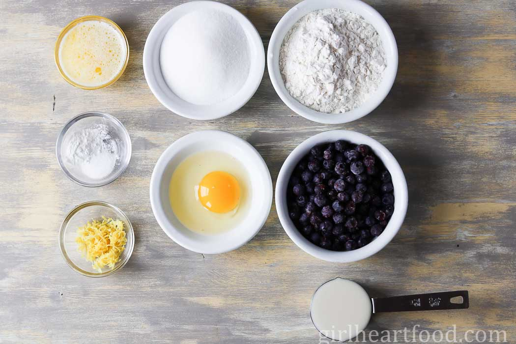 Ingredients for a blueberry donut recipe on a wooden board.