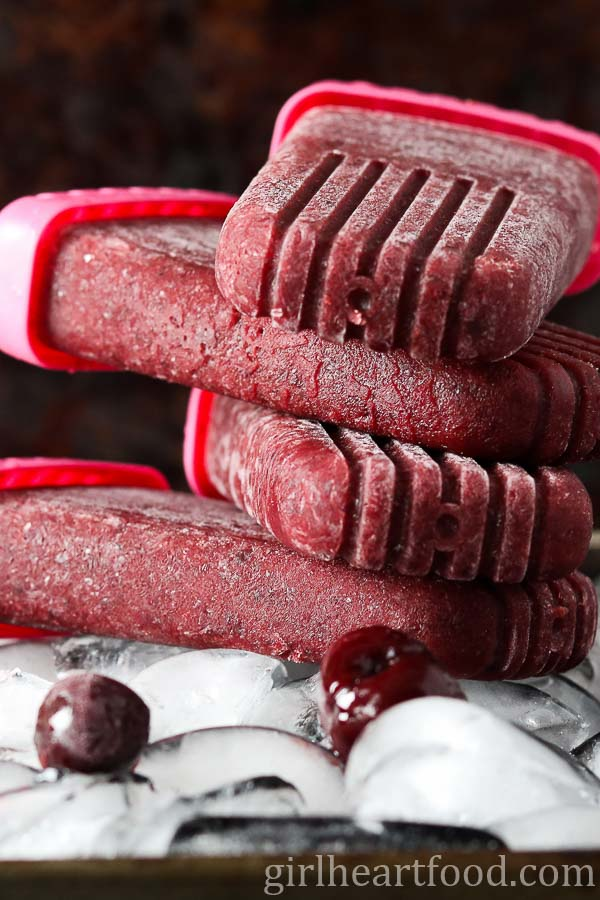 A stack of cherry vanilla ice pops on a tray of ice cubes.