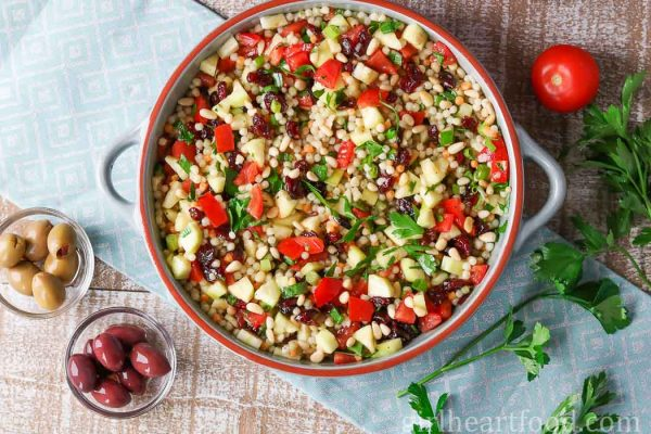 Overhead shot of Israeli couscous salad alongside some olives, tomato and parsley.