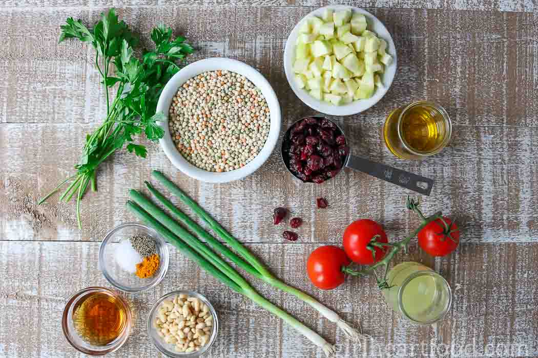 Ingredients for a couscous salad on a wooden board.