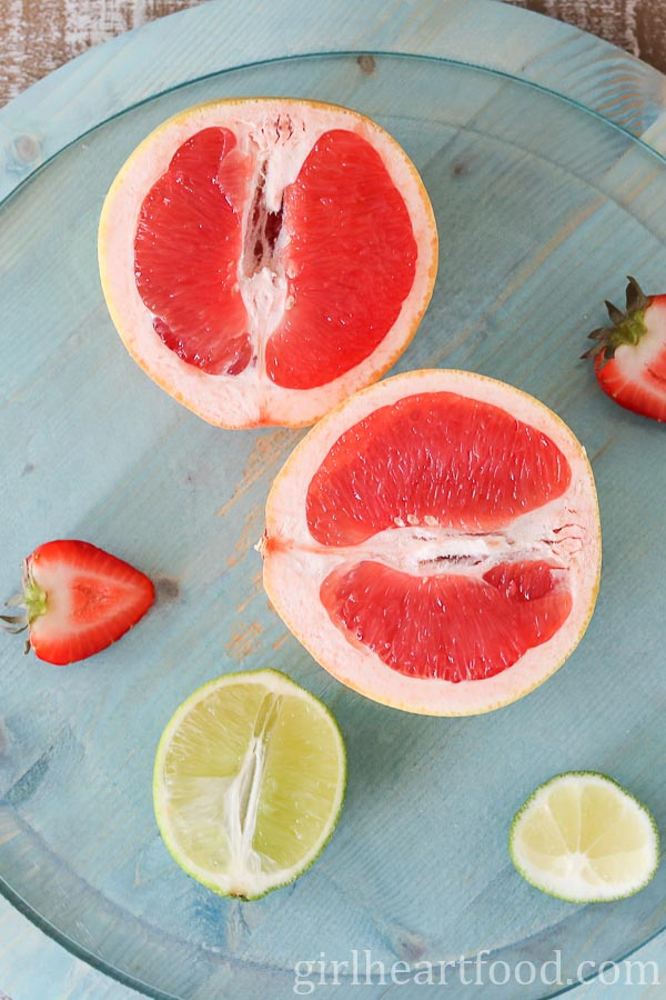 A cut grapefruit alongside some lime and strawberry.