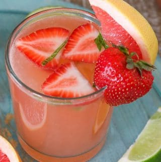 A glass of grapefruit rose sangria garnished with fresh strawberry and grapefruit.