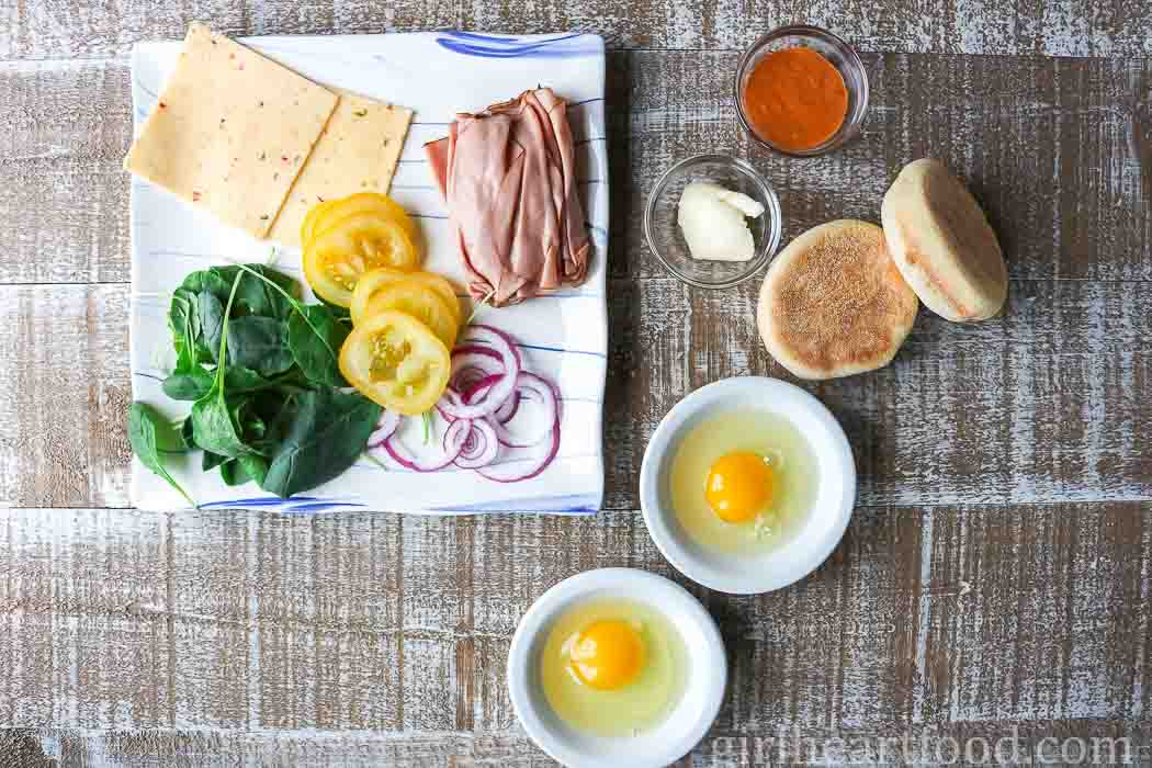 The ingredients for two ham and fried egg sandwiches on a board.