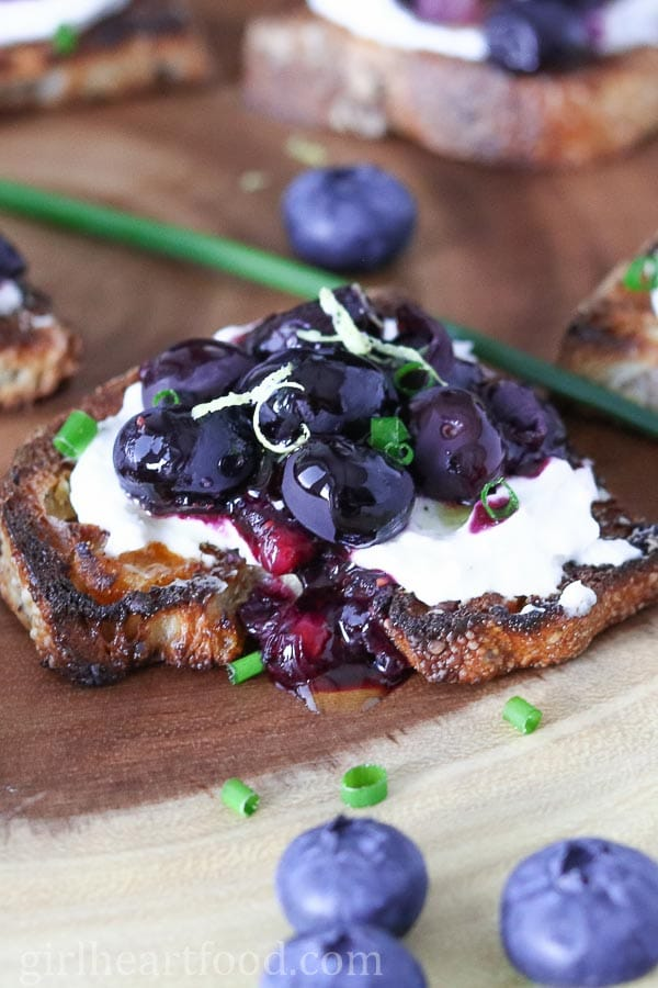 Roasted blueberry and goat cheese crostini recipe garnished with lemomn zest and chives.